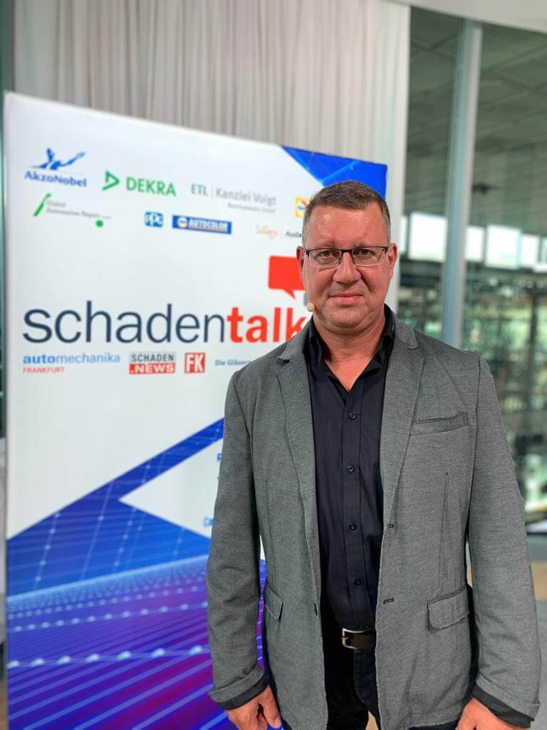 Herr Böge vor einem Plakat