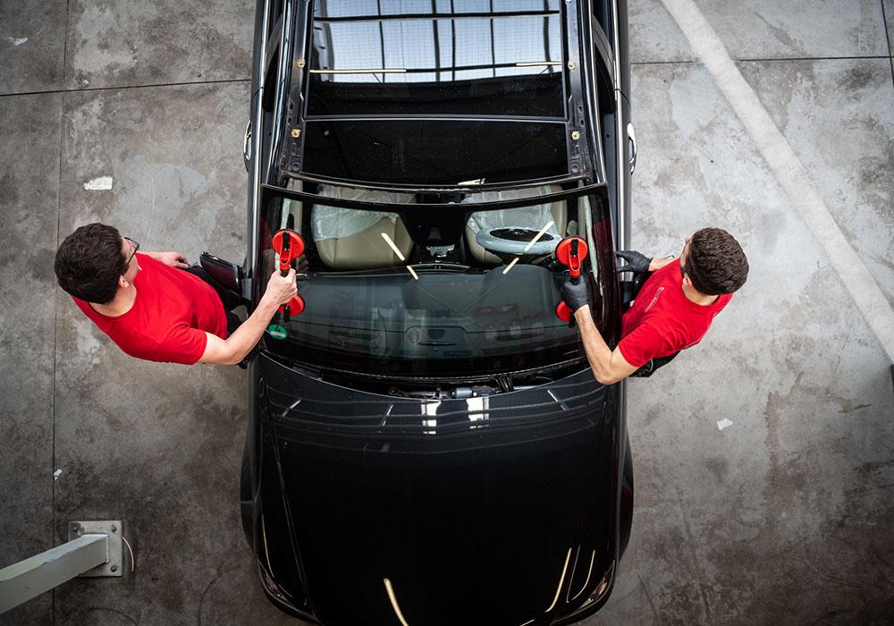 Eine Autoscheibe wird vom Auto gelöst und abgenommen.
