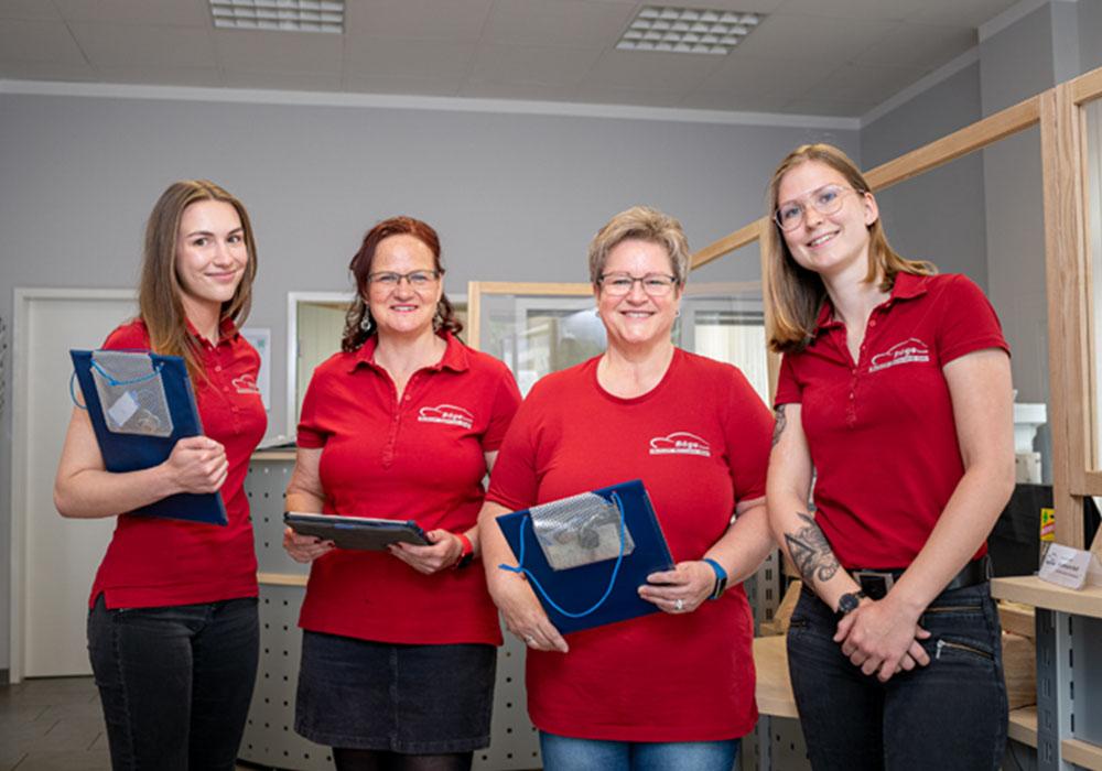 4 junge Frauen stehen in einem Büro und lächeln.