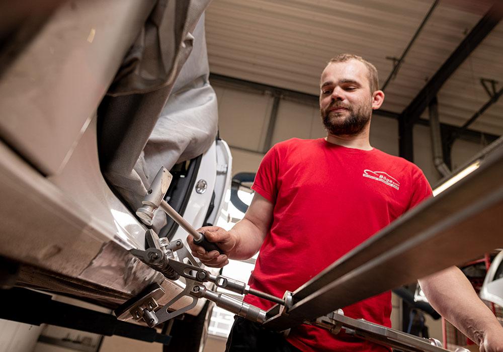 Ein junger Mann repariert gerade ein Auto.