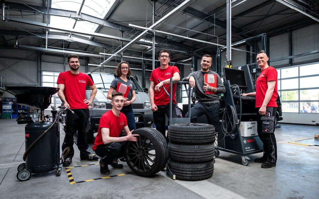 Das Team Leipzig Nord steht in einer großen Werkstatt und lächelt.