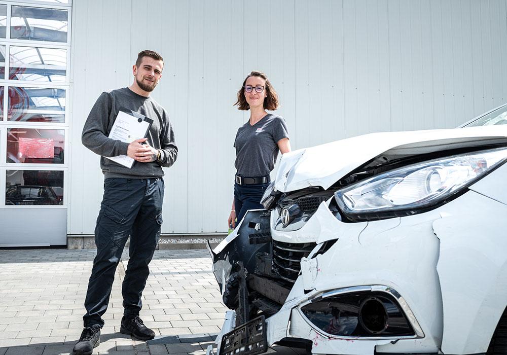 Ein Mann und eine Frau stehen vor einem kaputten Auto.