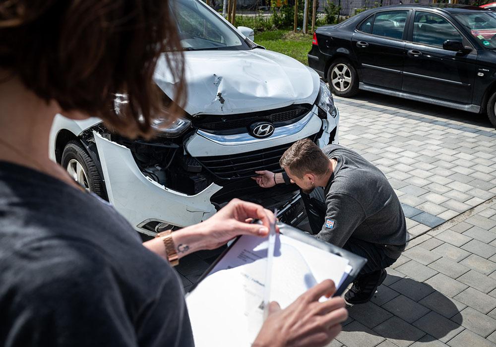 Ein Mann inspiziert ein kaputtes Auto.
