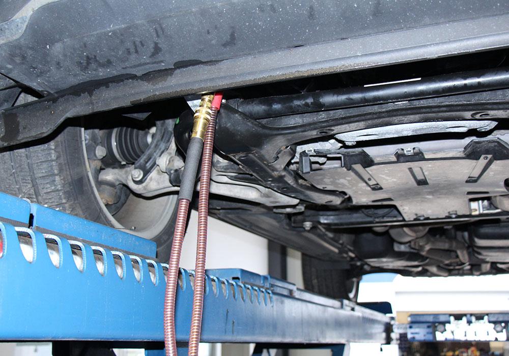 Eine Automatikgetriebeölspülung wird an einem Auto vorgenommen